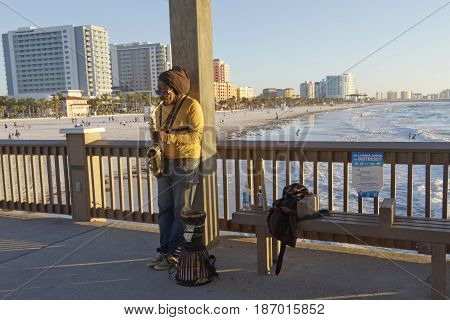 Clearwater Beach; Florida; USA - January 24, 2017: A busker plays the saxophone for tips on Pier 60 as people play on Clearwater Beach and in the Gulf of Mexico in the background