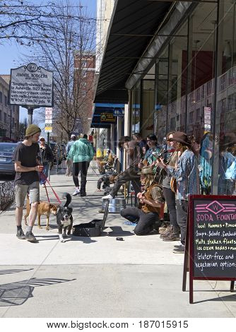 Asheville North Carolina USA - March 24, 2017: Buskers play music for tips on the street in front of the historic Woolworth Building one man walks two dogs past them and another man does push ups on the sidewalk nearby on a sunny day in downtown Asheville
