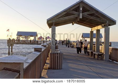 Clearwater Beach; Florida; USA - January 24, 2017: Sunset at Pier 60 on Clearwater Beach a 1080 foot fishing pier and recreational park with a bait house store telescopes and covered pavilions and a beach playground.