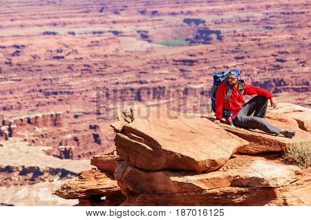 Hiker rests in Canyonlands National park in Utah USA