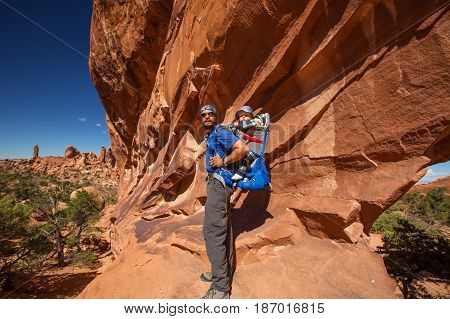 A Father With His Baby Son Near Double O Arch In Arches National Park In Utah, Usa