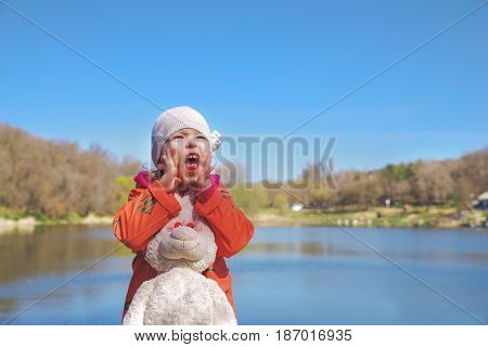 Closeup portrait of a screaming girl in the park on the background of the lake