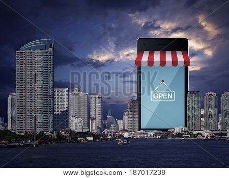 Modern smart mobile phone with on line shopping store sign modern office city tower river and sunset sky e-business concept