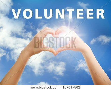 Volunteer concept. Woman holding hands in heart shape and text on sky background