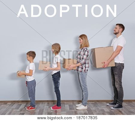 Adoption concept. Happy family with boxes standing against wall background