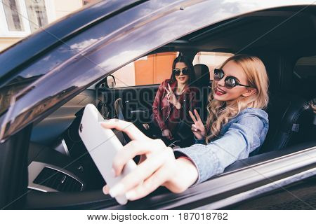Side View Of Four Beautiful Young Cheerful Women Making Selfie And Smiling While Sitting In Car Toge
