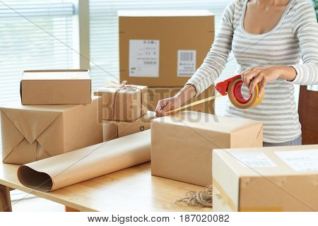 Cropped image of woman wrapping boxes to send via mail