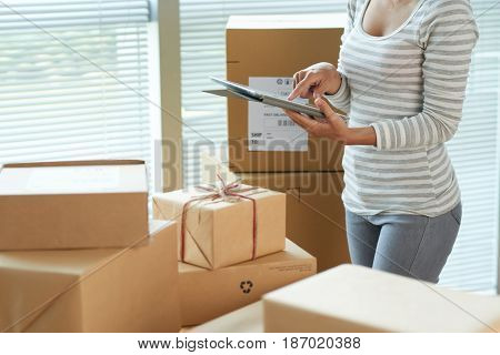 Business woman using tablet computer to control how many parcels she is shipping