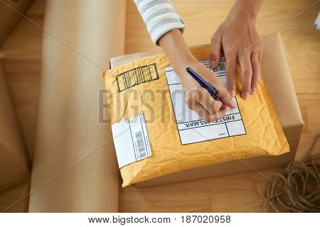 Hands of woman writing address on first class mail package