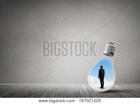 Businessman inside of light bulb in empty concrete room