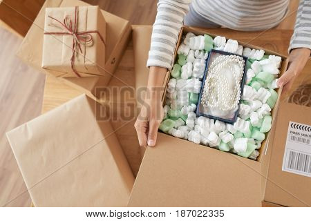 Woman opening many parcels she received, view from above