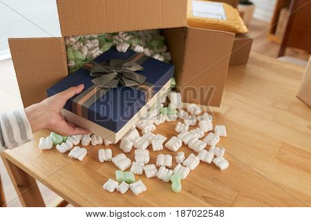 Hand of woman taking gift out of parcel