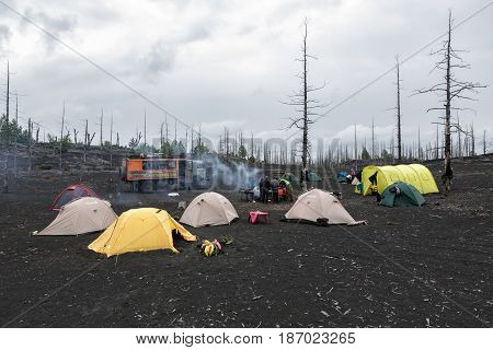 KAMCHATKA PENINSULA RUSSIA - June 25 2014: Tourist campground in Dead Wood on volcanic slag and ash eruptions Tolbachik Volcano - consequence of catastrophic eruption of volcano during on 1975-1976.