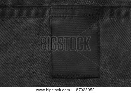 Black blank clothes label on black cloth as a background