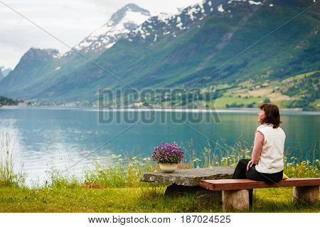 Woman Tourist Relaxing On Fjord Sea Shore, Norway