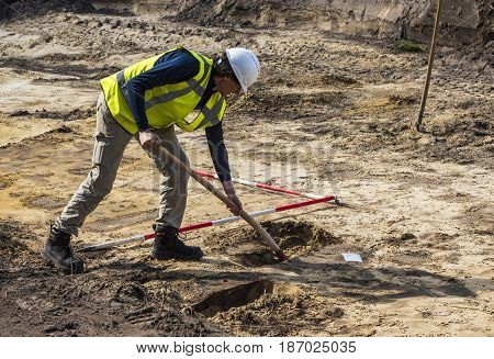 Driebergen The Netherlands - March 22 2017: Archeology excavation site with man digging in the ground in Driebergen The Netherlands.