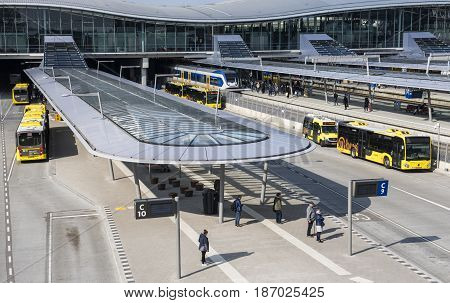 Utrecht The Netherlands - March 23 2017: Bus and railway station with yellow buses train and waiting travelers The Netherlands.