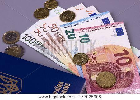 International Ukrainian Passport With Euro Banknotes Isolated On Gray Background.