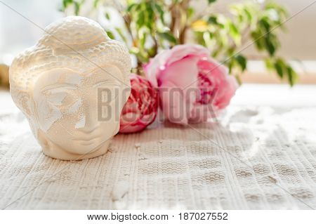 Buddha face. Buddha statue made of white marble with flowers. Concept of peace, calm and tranquility. Buddhist artifact for Zen style interior decor