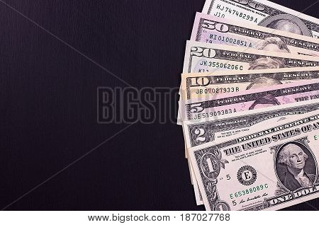 Pile Of Dollar Bills Of Different Denominations On Black Backgrond.