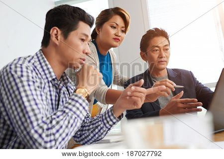 Concerned Asian business people reading information on laptop screen