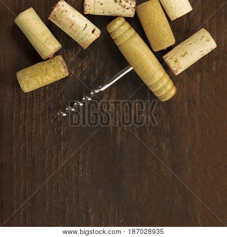 A square photo of an old-fashioned corkscrew with corks, shot from above on a dark wooden background texture with copy space. A design template for a wine list or a tasting invitation