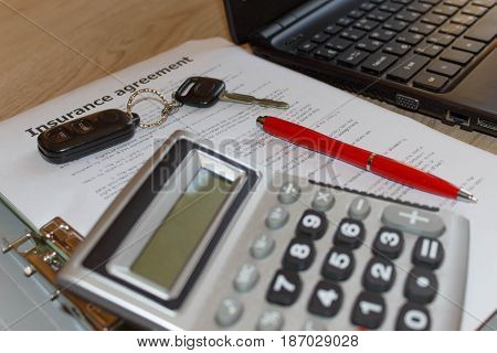 Insurance policy and key from the car. Insurance concept. Car insurance form with car keys pen Laptop and calculator