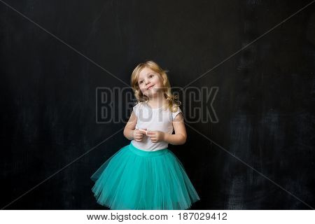 Young Girl Standing In Front Of Chalk Board