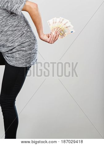 Rich finances miser concept. Man holding money behind his back studio shot on grey background