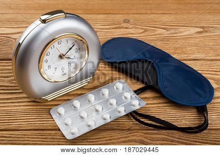 Alarm clock, mask and sleeping pills on a wooden background