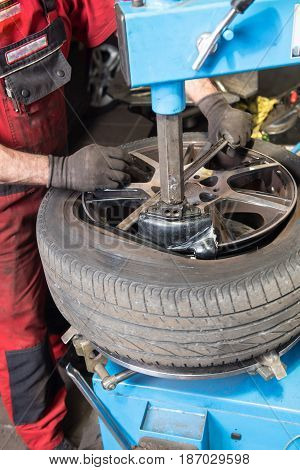 Man in Car repair levers a used tyre of the rim