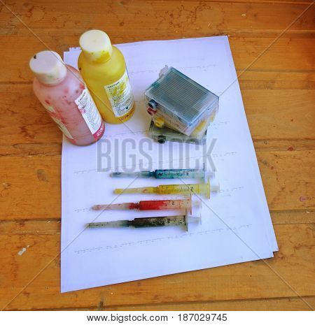 Set of Ink cartridges, refill paints in bottles and dirty syringes. On white paper. Jet printer maintenance.