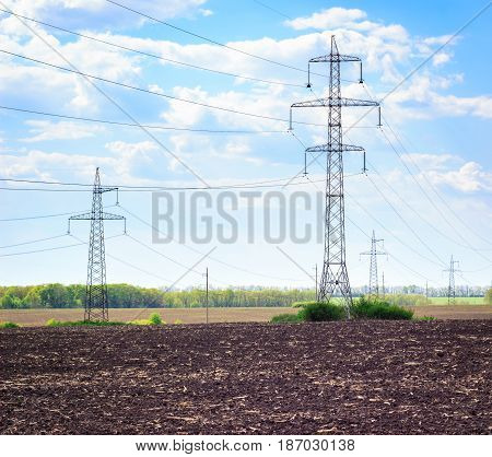 Wires stretch on metal high structures under a beautiful blue sky with white clouds