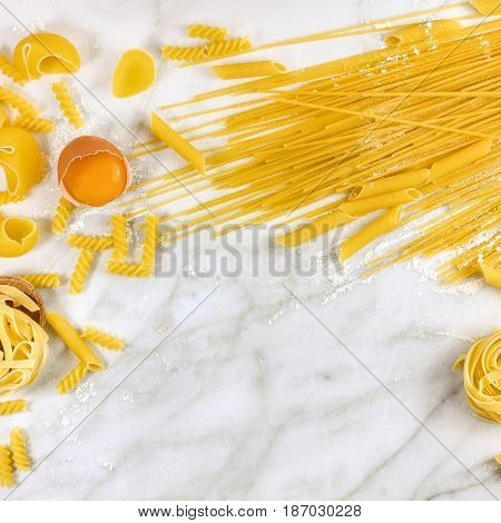 Various types of pasta on a white marble table with flour and an egg, forming a frame for text, square photo
