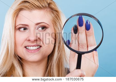 Woman Looking At Nails Through Magnifying Glass
