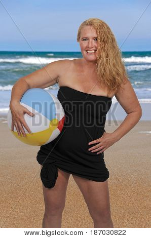 Beautiful young woman holding a beach ball