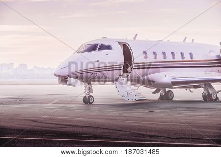 Private jet plane parking at the airport. Business aircraft at sunset.