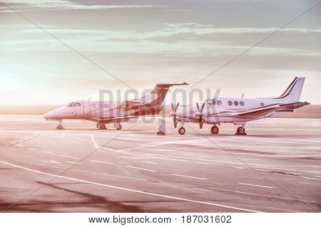 Private jet planes parking at the airport. Business aircrafts at sunset.