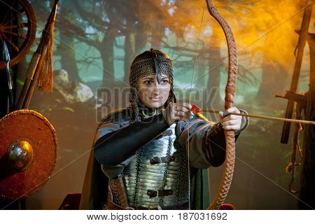 A woman in the costume of a warrior of the times of Kiev Russia in chain mail with a bow and arrows aiming