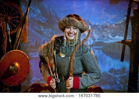 A smiling blonde woman in the costume of a warrior of the times of Kiev Rus in chain mail with a bow and arrows