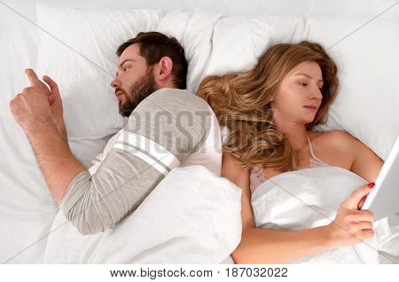 Young Couple In Bed Using Phone Lying Backs To Each Other.
