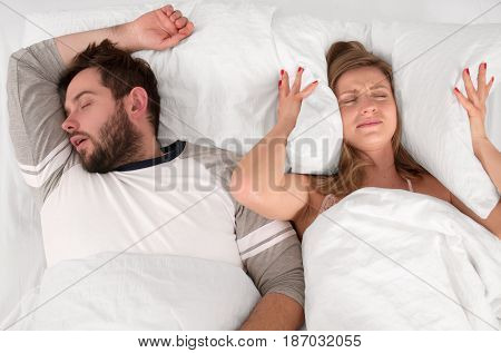 Couple in bed man snoring and woman can't sleep covering ears with pillow for snore noise