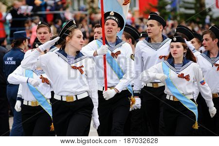Orel Russia - May 9 2017: Victory Day selebration. Young people in white uniform shirts marching with flag