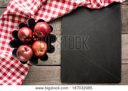 Ripe red apples on wooden board with red checkered towel around and accessories for baking. Copy space for text on dish from black slate.