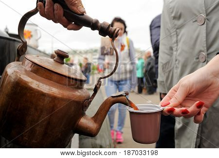 Orel Russia - May 9 2017: Victory Day selebration. Pouring tea from big old copper kettle