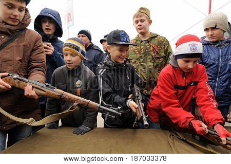 Orel Russia - May 9 2017: Victory Day selebration. Young boys playing with old guns