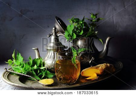 nettle tea with ginger and honey on a silver platter