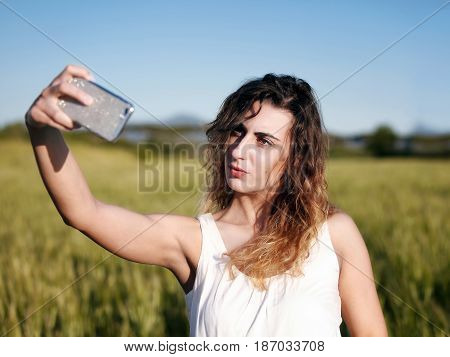A young blond girl at the park stretches out her arm and with a cell phone she takes a picture in the landscape