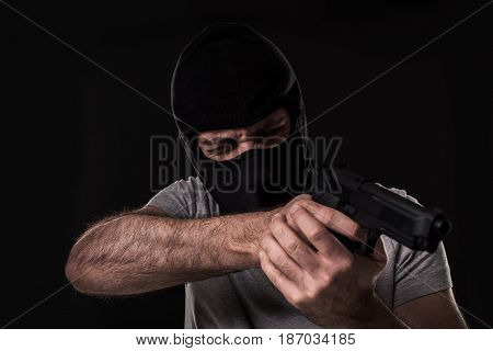 The robber in a mask with a gun pointed to the side on a black background. Man with a gun