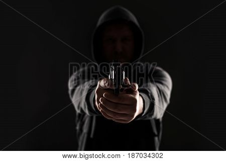 Masked robber with gun aiming into the camera against a black background. Man with a gun